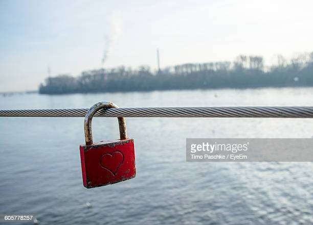 Close-Up Of Love Padlock Hanging On Rope By Sea Against Sky