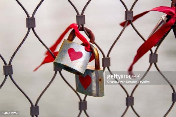Close-Up Of Love Padlocks Hanging On Chainlink Fence