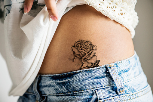 Closeup of lower hip tattoo of a woman 938938878