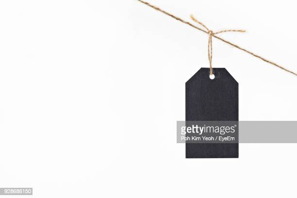 Close-Up Of Luggage Tag Hanging On White Background