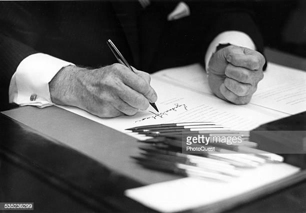 Closeup of Lyndon Johnson's hands, as he signs an Executive Order, Washington DC, 1968.