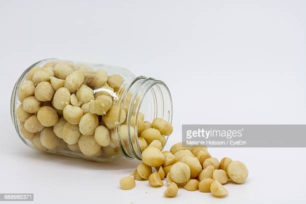 Close-Up Of Macadamia Nuts Spilling From Mason Jar Over White Background