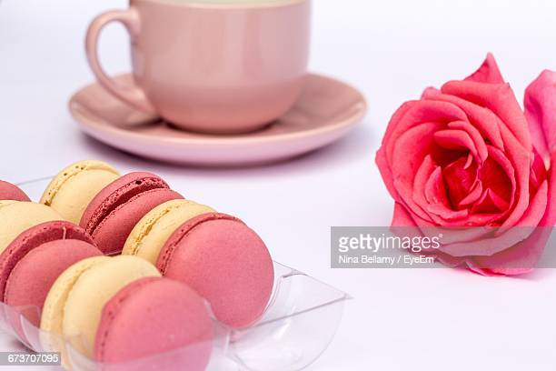 Close-Up Of Macaroons With Coffee Cup And Rose On White Background