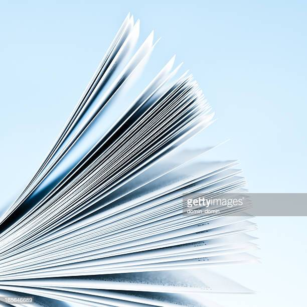 close-up of magazine pages on light blue background - magazine page stock photos and pictures