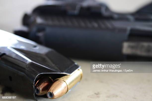 close-up of magazine with bullets by gun on table - ammunition magazine stockfoto's en -beelden