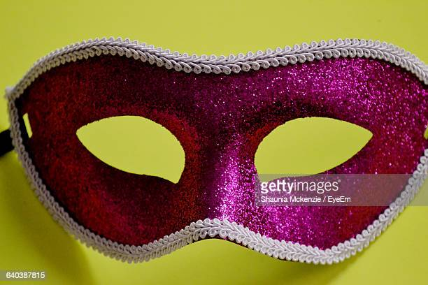 Close-Up Of Magenta Masquerade Mask Against Yellow Background