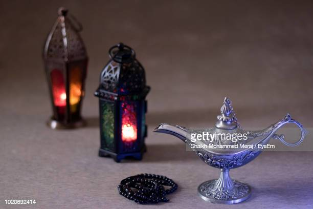 close-up of magic lamp with bead necklace and lanterns on table - lampara de aladino fotografías e imágenes de stock