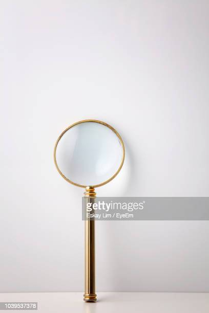 close-up of magnifying glass against white background - magnifying glass stock pictures, royalty-free photos & images