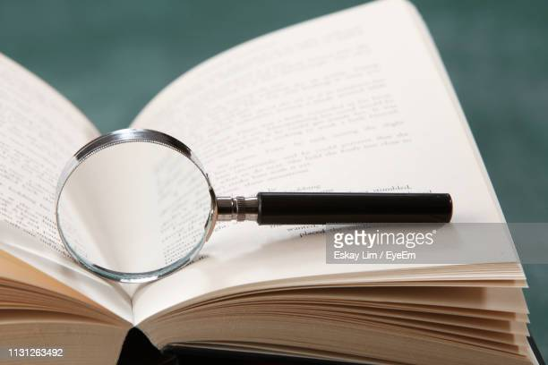 close-up of magnifying glass in open book on table - letteratura foto e immagini stock