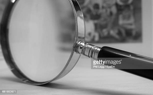 Close-Up Of Magnifying Glass On Table