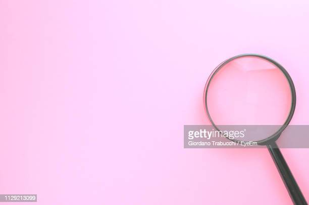 close-up of magnifying glass over pink background - magnifying glass stock pictures, royalty-free photos & images