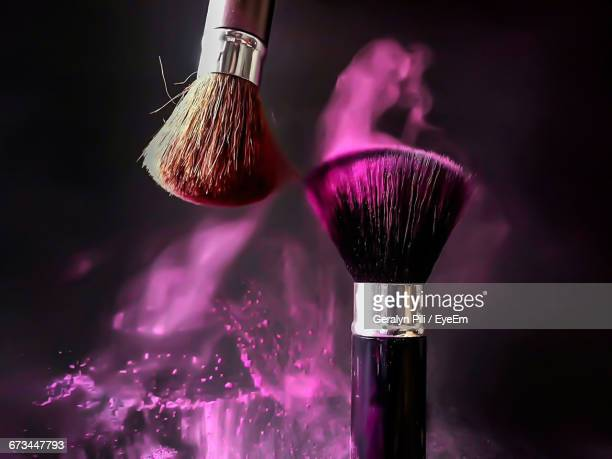 Close-Up Of Make-Up Brushes And Pink Powder Against Black Background