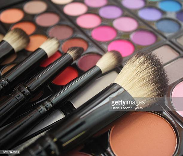Close-Up Of Make-Up Brushes On Colorful Eyeshadow Palette