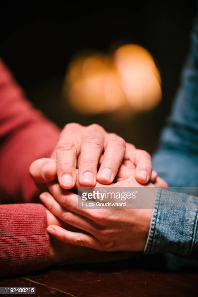 close-up of male and female holding hands in front of fireplace - clemence hollande photos et images de collection