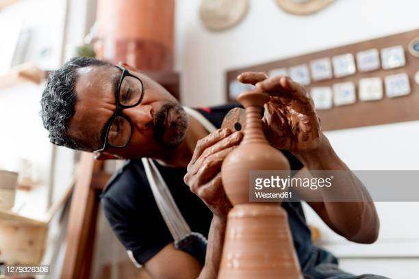 close-up of male artist making earthenware while sitting in workshop - artist stock pictures, royalty-free photos & images
