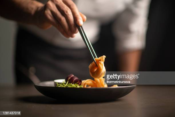 closeup of male chef in restaurant decorates  the meal - gourmet stock pictures, royalty-free photos & images