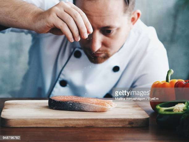 close-up of male chef seasoning raw fish on table - 魚介類 ストックフォトと画像
