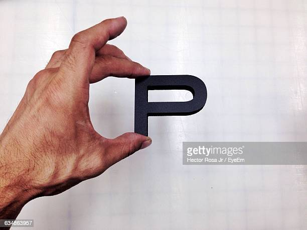 close-up of male hand holding letter p - letter p stock pictures, royalty-free photos & images