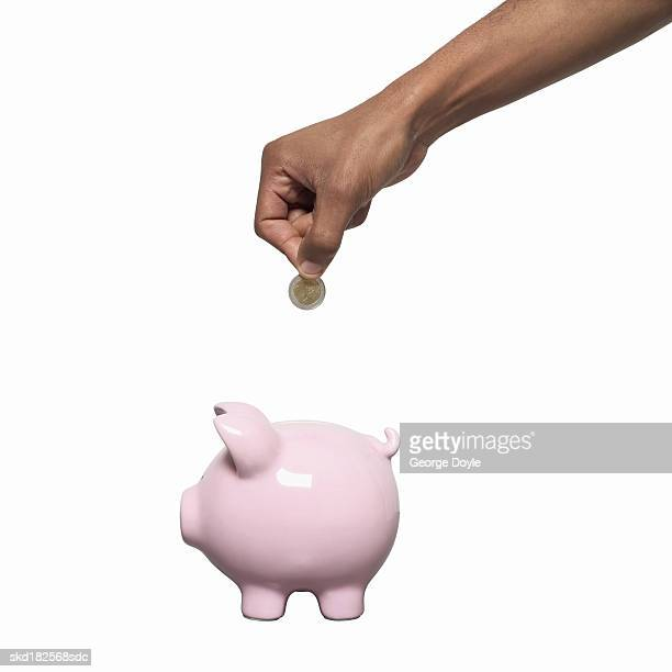 Close-up of male hand putting coins into piggy bank