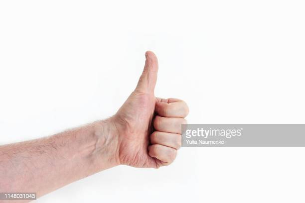 closeup of male hand showing thumbs up sign against - like button stock photos and pictures