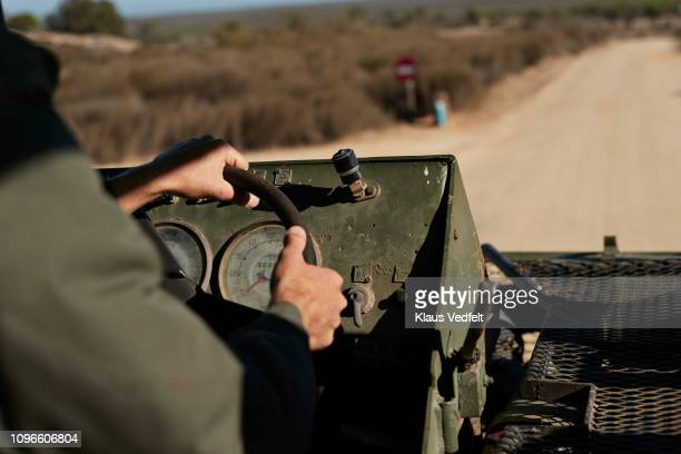 close-up of male hands on steering wheel of safari vehicle - khaki green stock pictures, royalty-free photos & images