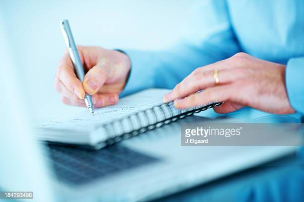 Closeup of male hands writing notes with a laptop