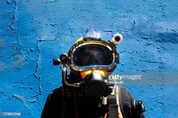 close-up of male instructor wearing diving suit standing against blue wall - diving sport stock pictures, royalty-free photos & images