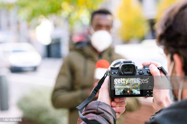 close-up of male operator filming reporter with camera - journalist stock pictures, royalty-free photos & images