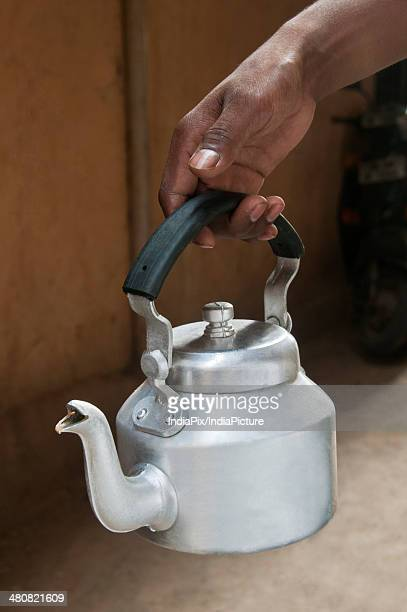 Close-up of male's hand holding an old fashioned tea kettle