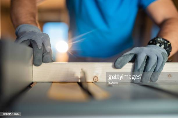 close-up of males hands using circular saw at construction site - glove stock pictures, royalty-free photos & images