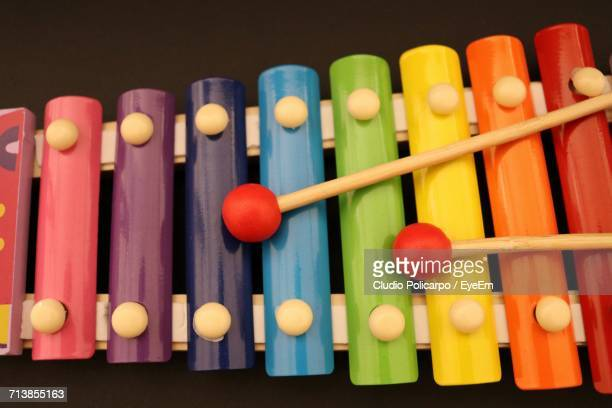 Close-Up Of Mallets With Colorful Xylophone Against Black Background