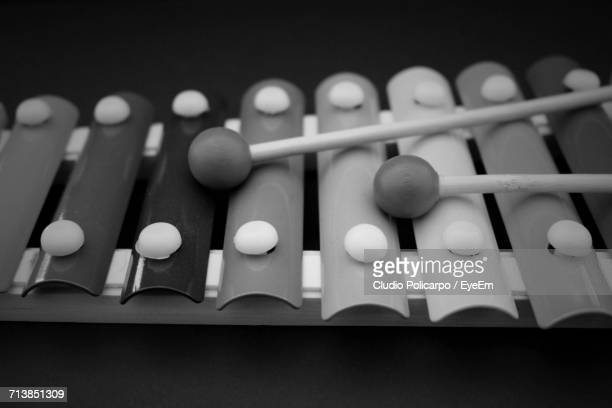 close-up of mallets with xylophone against black background - percussion instrument stock photos and pictures