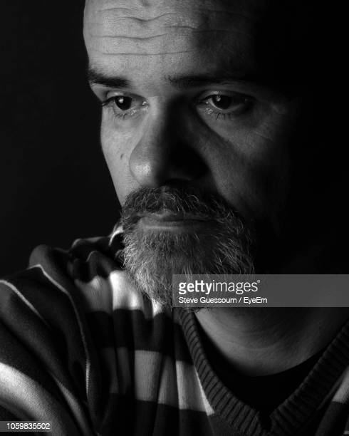 close-up of man against black background - steve guessoum stockfoto's en -beelden