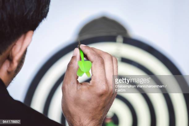 close-up of man aiming against dartboard - dartboard stock pictures, royalty-free photos & images