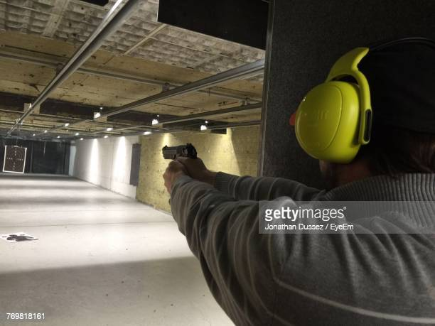 close-up of man aiming gun - sportschießen stock-fotos und bilder