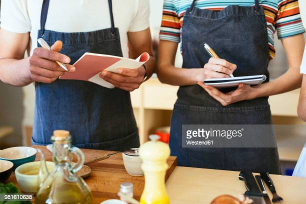 close-up of man and woman taking notes in a cooking workshop - homme maghrebin photos et images de collection