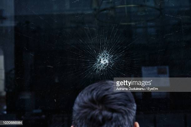 Close-Up Of Man At Cracked Window