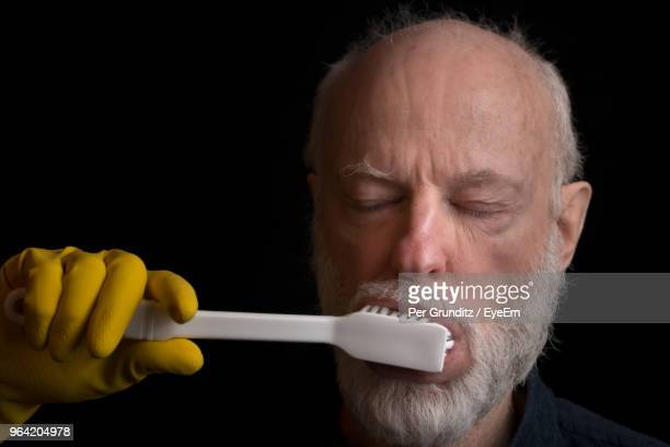 Close-Up Of Man Brushing Teeth Over Black Background