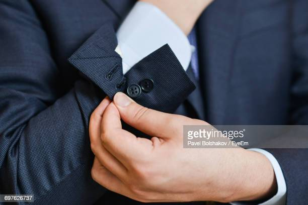 close-up of man buttoning sleeve - long sleeved stock pictures, royalty-free photos & images