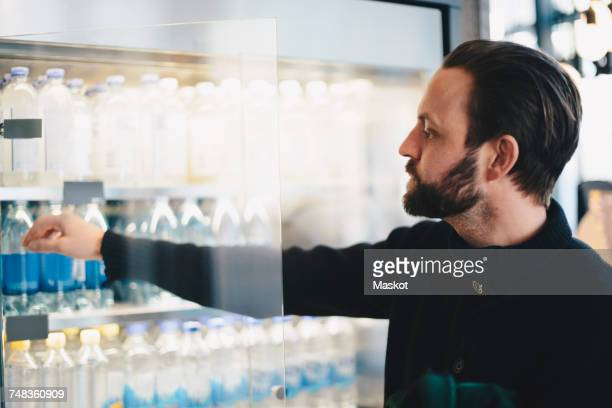 Close-up of man buying water bottle from glass cabinet at store