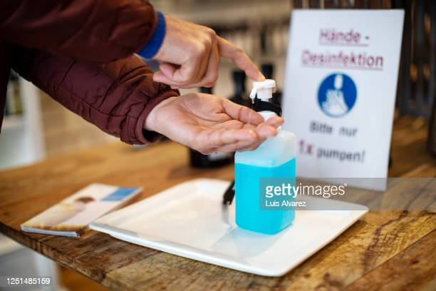 close-up of man cleaning hands with hand sanitizer at pharmacy - 消毒薬 ストックフォトと画像
