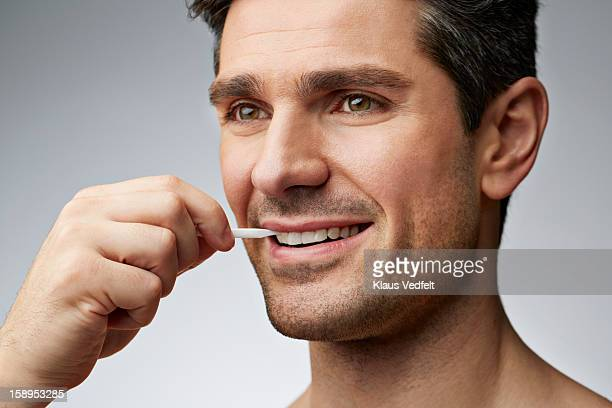 Close-up of man cleaning teeth with toothpick