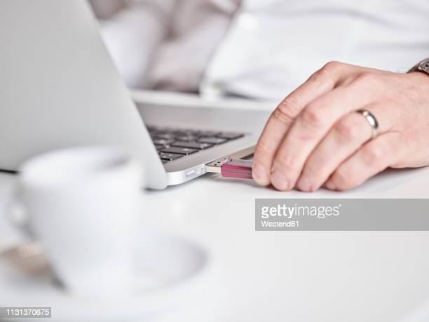 close-up of man connecting usb stick to laptop - plugging in stock pictures, royalty-free photos & images