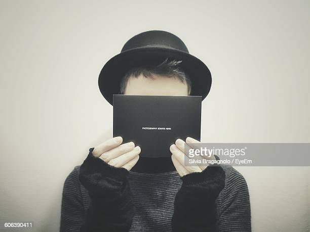 Close-Up Of Man Covering Face With Paper Against Wall