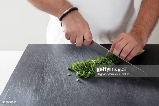 Close-Up Of Man Cutting Vegetable On Cutting Board