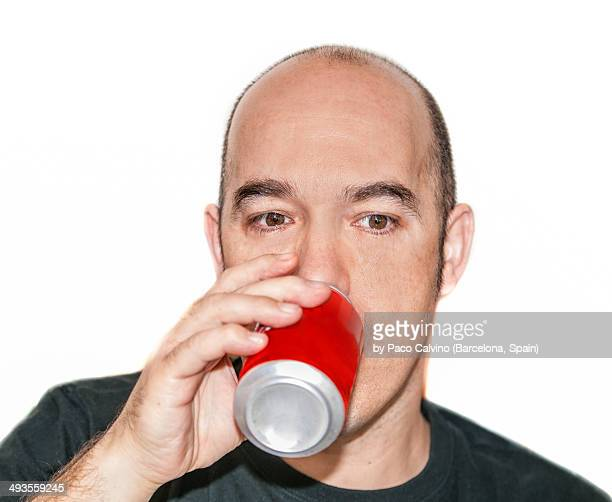 Closeup of man drinking from a red can