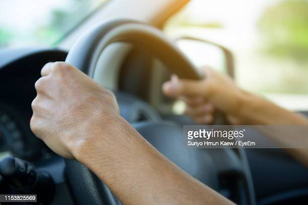 close-up of man driving car - steering wheel stock pictures, royalty-free photos & images