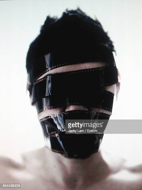 Close-Up Of Man Face Covered With Film Reel Against White Background