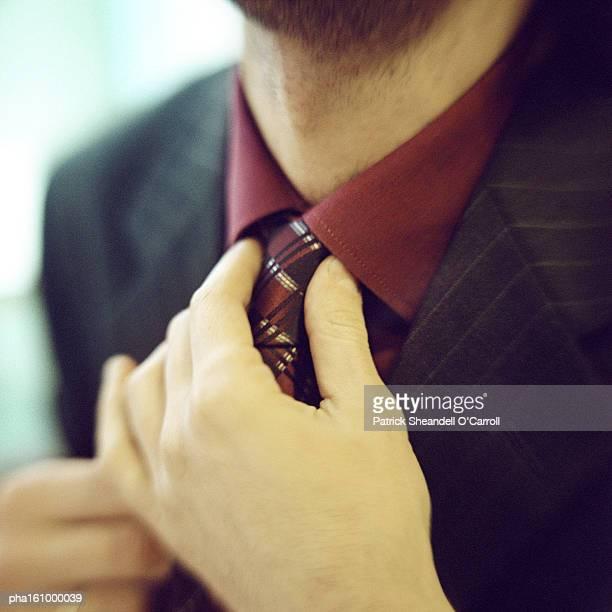 Close-up of man fixing tie.