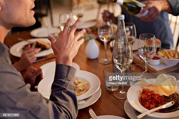 Close-up of man gesticulating at dinner